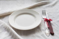 Tableware, white plate, fork, knife on a white tablecloth Royalty Free Stock Photography