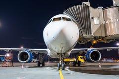Tablier d'avion à la passerelle de stationnement à l'aéroport la nuit Photo stock