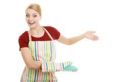 Tablier de cuisine de femme au foyer faisant le geste bienvenu de invitation Photo stock