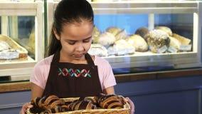 Tablier de port adorable de petite fille fonctionnant à la boulangerie souriant à l'appareil-photo banque de vidéos