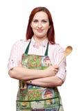 Tablier s'usant de cuisinière de Madame, retenant une cuillère en bois Photos stock