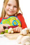 Tablier s'usant de petite fille coupant en tranches des champignons de couche Photo libre de droits