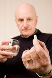 Tablilla o píldora mayor de la explotación agrícola de un más viejo hombre con agua Fotografía de archivo libre de regalías