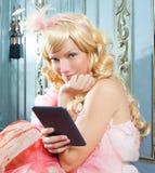 Tablilla rubia del ebook de la lectura de la mujer de la princesa de la manera fotos de archivo libres de regalías