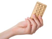 Tablillas (píldoras de control de la natalidad) en la mano Foto de archivo