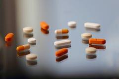 Tablillas y píldoras sobre el vidrio Fotos de archivo