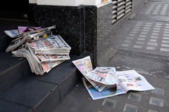 Tabloid newspapers abandoned in a shop doorway. LONDON, UK - MAY 25, 2014: Tabloid newspapers in a shop doorway on May 25, 2014. Headlines in the Daily Mirror Stock Photo