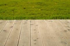 Tablones de madera con la hierba verde Fotos de archivo