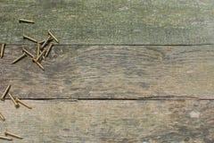 Tablones de madera resistidos de la plataforma con los tornillos de madera de cobre amarillo a lo largo del lado izquierdo foto de archivo