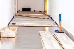 Tablones del piso laminado y de las herramientas para instalarlas foto de archivo