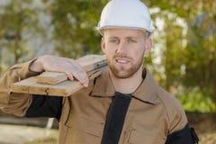 Tablones que llevan del carpintero joven en hombro imagen de archivo libre de regalías