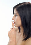 Taboo. Young woman with finger on lips stock photos