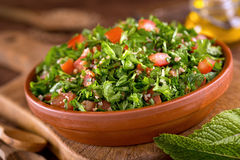 Tabouli. A bowl of delicious fresh tabouli with parsley, mint, tomato, onion, olive oil, lemon juice, and bulgar wheat Royalty Free Stock Image