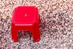 Tabouret rouge dans peu de plancher en pierre Image libre de droits