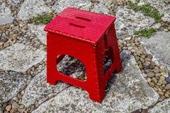 Tabouret rouge sur un chemin de jardin photographie stock libre de droits