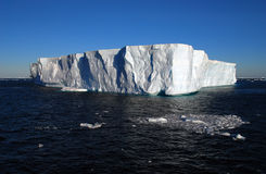 Tabular iceberg floating in the blue ocean. Full sun Stock Photos