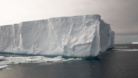 Tabular Iceberg in Gloomy Antarctic Conditions. An impressively big Iceberg looming high over dark Antarctic waters, against the backdrop of a stormy sky royalty free stock photography