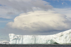 Tabular iceberg with linticular cloud, Antarctica Royalty Free Stock Image