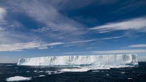 Tabular Iceberg Under Sunny, Blue Skies. A large tabular iceberg under deep blue skies Stock Photo