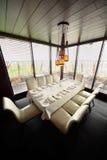 Tabule y diez sillas blancas en restaurante vacío Imagenes de archivo