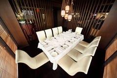 Tabule y diez sillas blancas en restaurante vacío Fotografía de archivo libre de regalías