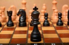 Tabuleiro de xadrez com o rei na parte dianteira e os penhores no fundo Fotos de Stock Royalty Free