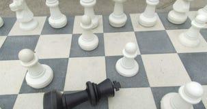 Tabuleiro de xadrez gigante com o rei preto caído filme