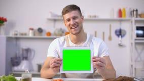 Tabuleta alegre da terra arrendada do homem com tela verde, cozinhando blogues e molde dos apps video estoque