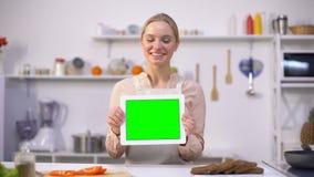 Tabuleta alegre da terra arrendada da mulher com tela verde, cozinhando blogues e molde dos apps filme