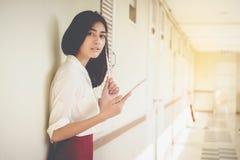 Tabuleta asiática do uso dos homens de negócios das mulheres para contactar o trabalho e o negócio fotografia de stock