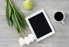 A tabuleta branca com flores brancas, as ma??s verdes e uma x?cara de caf? encontra-se em uma tabela de madeira branca imagem de stock royalty free