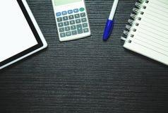 Tabuleta, calculadora, pena e bloco de notas de Digitas no backgro de madeira escuro fotos de stock royalty free