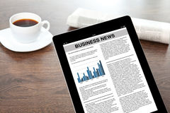 Tabuleta com notícias de negócios em uma tela em uma tabela  Fotografia de Stock Royalty Free