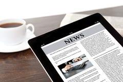 Tabuleta com notícias de negócios na tela em uma tabela em um homem de negócios Foto de Stock Royalty Free