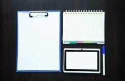 Tabuleta com o bloco de notas no fundo escuro foto de stock