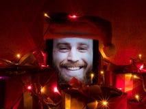 Tabuleta com o homem farpado feliz na tela e no tampão de Santa nele com atributos do Natal ao redor Fotos de Stock