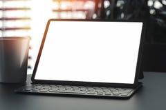 Tabuleta com a tela e o teclado brancos vazios na tabela workspace rendição 3d foto de stock