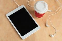Tabuleta com a tela preta vazia com fones de ouvido e uma opinião superior da xícara de café foto de stock