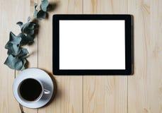 Tabuleta com um monitor limpo do modelo da tela vazia com um ramo do eucalipto e uma xícara de café em um fundo de madeira imagens de stock royalty free