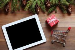 A tabuleta com um presente e o carrinho de compras pequeno na tabela de madeira Imagem de Stock Royalty Free