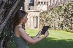 Tabuleta da leitura da mulher e para apreciar o resto em um parque sob a ?rvore imagens de stock royalty free
