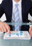 Tabuleta de Comparing Graphs On Digital do homem de negócios no escritório Fotos de Stock Royalty Free