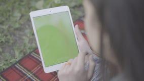 Tabuleta de datilografia da jovem mulher exterior video estoque