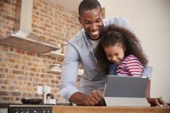 Tabuleta de And Daughter Using Digital do pai na cozinha em casa fotografia de stock