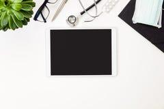 Tabuleta de Digitas cercada pelo equipamento médico pela planta na tabela Imagens de Stock