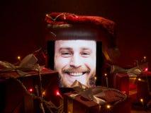 Tabuleta de Digitas com o homem farpado feliz na tela e no tampão de Santa nele com atributos do Natal ao redor Fotografia de Stock Royalty Free