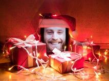 Tabuleta de Digitas com o homem farpado feliz na tela e no tampão de Santa nele com atributos do Natal ao redor Imagens de Stock