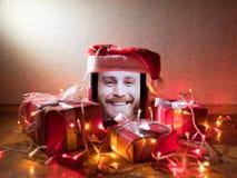 Tabuleta de Digitas com o homem farpado na tela e no chapéu de Santa nele com as caixas e as luzes de presentes do Natal ao redor Fotografia de Stock