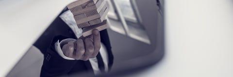 Tabuleta de Digitas com reflexão de um homem de negócios que coloca b de madeira Foto de Stock