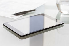 Tabuleta de Digitas na tabela de vidro moderna no escritório Foto de Stock